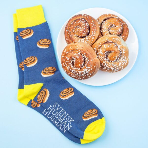 "Blue and Yellow ""Kanelbulle"" Cinnamon Roll Socks next to plate of Swedish Cinnamon Rolls"