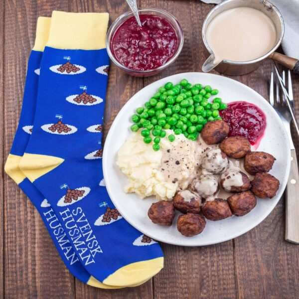 Blue and yellow Swedish meatball socks next to plate of meatballs with potatoes, peas, and lingonberries.